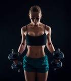 Портрет молодой женщины фитнеса в sportswear делая разминку с гантелями на черной предпосылке Загоренная сексуальная атлетическая Стоковое фото RF