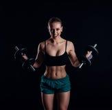 Портрет молодой женщины фитнеса в sportswear делая разминку с гантелями на черной предпосылке Загоренная сексуальная атлетическая Стоковая Фотография RF