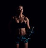 Портрет молодой женщины фитнеса в sportswear делая разминку с гантелями на черной предпосылке Загоренная сексуальная атлетическая Стоковое Фото