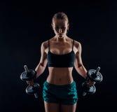 Портрет молодой женщины фитнеса в sportswear делая разминку с гантелями на черной предпосылке Загоренная сексуальная атлетическая Стоковые Фото
