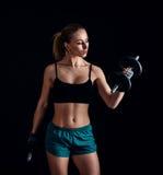 Портрет молодой женщины фитнеса в sportswear делая разминку с гантелями на черной предпосылке Загоренная сексуальная атлетическая Стоковое Изображение