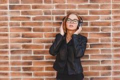 Портрет молодой женщины blondhair жизнерадостной наслаждаясь музыкой в наушниках над предпосылкой стены grunge кирпича стоковое изображение