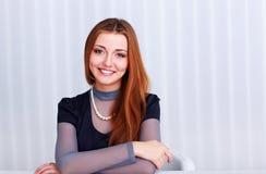 Портрет молодой жизнерадостной женщины сидя на таблице Стоковые Фотографии RF