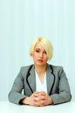 Портрет молодой заботливой коммерсантки сидя на таблице Стоковые Фото