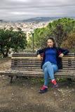 Портрет молодой и привлекательной женщины сидя на стенде на пасмурный день Стоковое Фото