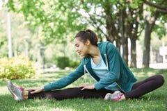 Портрет молодой и sporty женщины в sportswear делая йогу или протягивая работает Стоковая Фотография