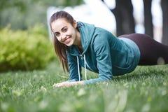 Портрет молодой и sporty женщины в sportswear делая йогу или протягивая работает Стоковые Фотографии RF