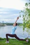Портрет молодой и sporty женщины в sportswear делая йогу или протягивая работает Стоковые Изображения