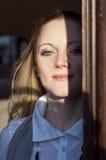 Портрет молодой кавказской белокурой женщины смотря из входа с Lit стороны половинным и частично в тени Стоковое Изображение RF