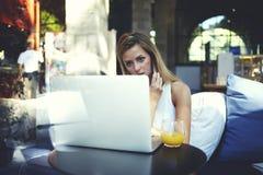 Портрет молодой коммерсантки имея переговор мобильного телефона пока сидящ перед открытым портативным компьютером Стоковые Изображения RF