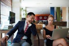 Портрет молодой коммерсантки работая на портативном компьютере пока сидящ с ее коллегой человека в современном интерьере Стоковое фото RF