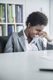Портрет молодой коммерсантки сидя на таблице и смеясь над с ее головой в ее руках Стоковое Фото