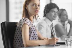 Портрет молодой коммерсантки с коллегами в встрече Стоковая Фотография
