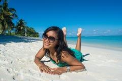Портрет молодой красивой азиатской девушки кладя на ее живот на пляже и усмехаясь на камере Стоковая Фотография