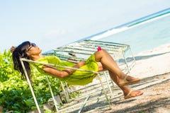 Портрет молодой красивой азиатской девушки ослабляя в гамаке на тропическом пляже Стоковое Изображение