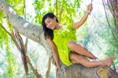 Портрет молодой красивой азиатской девушки сидя на баньяне усмехаясь на камере и держа ветвь Стоковое Изображение RF