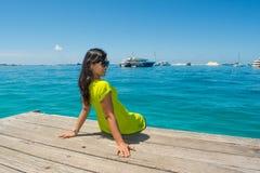 Портрет молодой красивой азиатской девушки сидя на пристани смотря назад Стоковое Изображение