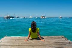 Портрет молодой красивой азиатской девушки сидя на пристани смотря на океан Стоковая Фотография RF