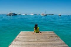 Портрет молодой красивой азиатской девушки сидя на пристани смотря океан Стоковые Изображения RF