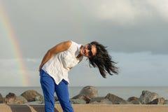 Портрет молодой красивой азиатской женщины смеясь над стоящей близко радугой Стоковые Фото