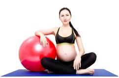 Портрет молодой красивой беременной женщины, сидя на циновке йоги с fitball стоковые изображения