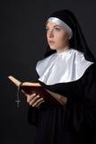 Портрет молодой красивой библии чтения монашки женщины над серым цветом Стоковая Фотография