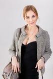 Портрет молодой красивой блондинкы бизнес-леди в черном платье и с сумкой на серой предпосылке Стоковые Фотографии RF