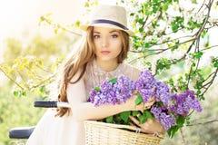 Портрет молодой красивой девушки в шляпе с длинными волосами на винтажном велосипеде держа цветки фасонируемая женщина Стоковые Изображения RF