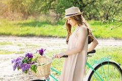 Портрет молодой красивой девушки в шляпе с длинными волосами с цветками в корзине на винтажном велосипеде фасонируемая женщина Стоковая Фотография