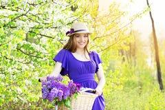 Портрет молодой красивой девушки в шляпе с длинными волосами с цветками в корзине на винтажном велосипеде фасонируемая женщина Стоковое фото RF
