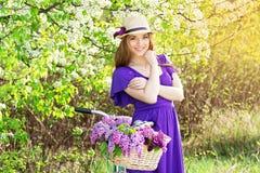 Портрет молодой красивой девушки в шляпе с длинными волосами с цветками в корзине на винтажном велосипеде фасонируемая женщина Стоковое Фото
