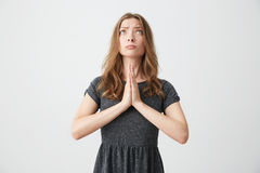 Портрет молодой красивой девушки смотря вверх молящ над белой предпосылкой Стоковая Фотография