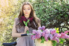 Портрет молодой красивой девушки с длинными волосами в ярком платье на винтажном велосипеде держа цветки фасонируемая женщина Стоковое Изображение RF