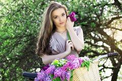 Портрет молодой красивой девушки с длинными волосами в ярком платье на винтажном велосипеде держа цветки фасонируемая женщина Стоковое фото RF