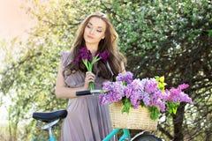 Портрет молодой красивой девушки с длинными волосами в ярком платье на винтажном велосипеде держа цветки фасонируемая женщина Стоковое Изображение