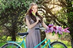 Портрет молодой красивой девушки с длинными волосами в ярком платье на винтажном велосипеде держа цветки фасонируемая женщина Стоковая Фотография RF