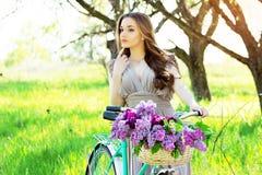 Портрет молодой красивой девушки с длинными волосами в ярком платье с цветками в корзине на винтажном велосипеде фасонируемая жен Стоковые Изображения RF