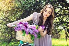 Портрет молодой красивой девушки с длинными волосами в ярком платье с цветками в корзине на винтажном велосипеде фасонируемая жен Стоковое Фото