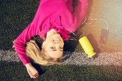 Портрет молодой красивой девушки фитнеса белокурых волос лежит на зеленой траве стадиона с телефоном и спорт разливают по бутылка Стоковые Изображения RF