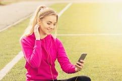 Портрет молодой красивой девушки фитнеса белокурых волос используя ее телефон на стадионе Деятельность при спорта лета Зеленая тр Стоковые Изображения