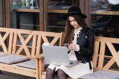 Портрет молодой красивой женщины одел внутри с стилем используя мобильный телефон во время работы на портативном портативном комп Стоковое Изображение RF