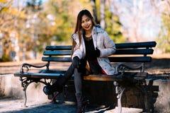 Портрет молодой красивой женщины сидя на стенде в стильном теплом обмундировании в солнечном дне осени в парке Вскользь образ жиз Стоковое Изображение RF