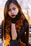 Портрет молодой красивой женщины сидя на стенде в стильном теплом обмундировании в солнечном дне осени в парке Вскользь образ жиз Стоковое фото RF