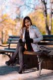 Портрет молодой красивой женщины сидя на стенде в стильном теплом обмундировании в солнечном дне осени в парке Вскользь образ жиз Стоковые Изображения RF