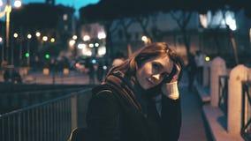Портрет молодой красивой женщины смотря камеру и делая вверх по волосам Повороты девушки, идут прочь в город вечера Стоковые Изображения