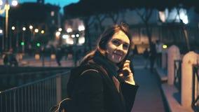 Портрет молодой красивой женщины смотря камеру и делая вверх по волосам Повороты девушки, идут прочь в город вечера Стоковое фото RF
