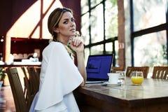 Портрет молодой красивой женщины Швеции ослабляя после работы на ее портативном компьютере во время перерыва на чашку кофе Стоковая Фотография RF