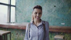 Портрет молодой красивой кавказской женщины в современном coworking космосе Коммерсантка смотря камеру, усмехаясь, сток-видео