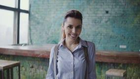 Портрет молодой красивой кавказской женщины в современном coworking космосе Коммерсантка смотря камеру, усмехаясь, Стоковые Изображения