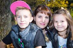 Портрет молодой красивой усмехаясь женщины с длинными волосами и внешнее Счастливая мама и девушка детей обнимая на природе стоковое фото